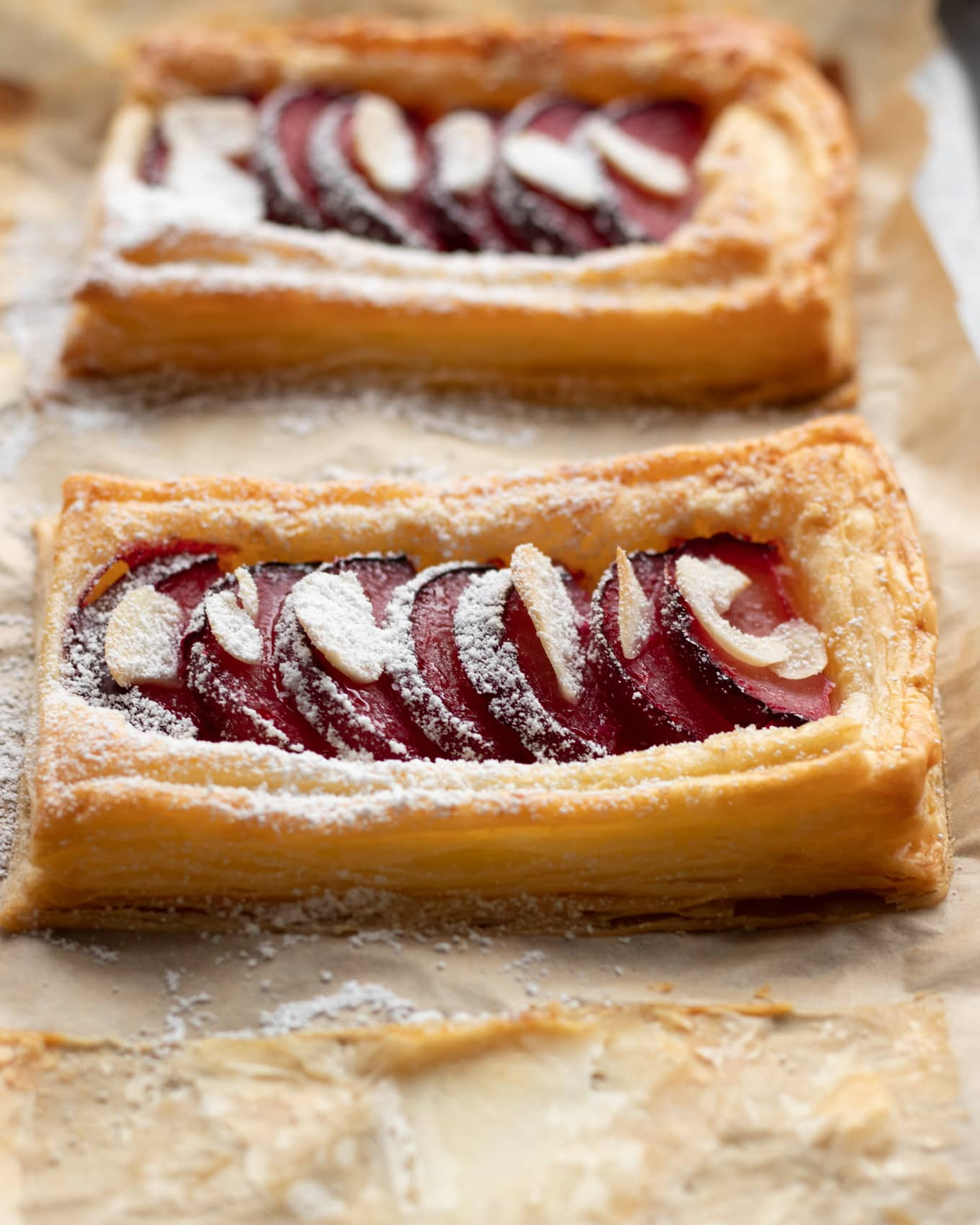 Plum tarts with slices almond and a dust of icing sugar
